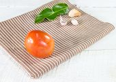 Tomato Garlic And Lime Leaves On A Napkin At Wood Background