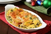 picture of butternut  - Butternut squash gratin with spinach and cheeses on a holiday table - JPG