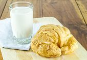 Breakfast Croissant Bread With Milk On Napkin And On A Wooden Board