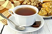 Tea in white cup with different cookies on light board