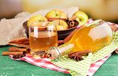 Composition of apple cider with cinnamon sticks, fresh apples on wooden table, on bright background