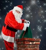 Closeup of Santa Claus placing his bag of toys into a chimney. Vertical format over a starry night time background.