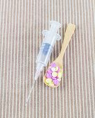 Syringe With Needle And Different Pills In Wooden Spoon