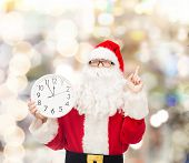 christmas, holidays and people concept - man in costume of santa claus with clock showing twelve pointing finger up over lights background