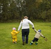 pic of misbehaving  - Mother walking with two children. The girl walks nicely by her side the boy misbehaves.