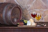 Glasses and bottles of wine, cheese on old barrel with iron rings