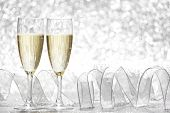Two champagne glasses and decoration on silver bokeh background