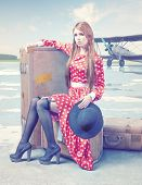 The beautiful young woman, waiting on the luggage in a retro airport.
