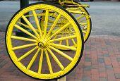 stock photo of wagon wheel  - Yellow Wooden wheels on an old wagon - JPG