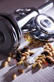 Dumbbell and colorful pills, tablets, on color wooden background