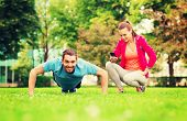 fitness, sport, training, technology and lifestyle concept - smiling man with personal trainer doing exercise outdoors