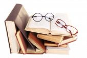Books in a mess and pair of glasses isolated on white