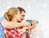 repair, interior design, building, renovation and family concept - smiling couple drilling hole in wall at home