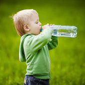 little boy drinks mineral water