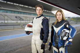 pic of race track  - Motor cyclist and a race car driver posing in the pit box in front of the grand stand of a race track - JPG