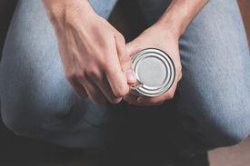 image of tin man  - A man is opening a tin with a tin opener - JPG