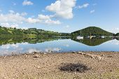 stock photo of barbie  - BBQ ashes by beautiful lake on calm idyllic summer morning with cloud reflections - JPG