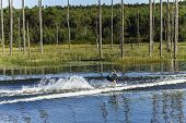 stock photo of ski boat  - Young teen girl learns to water-ski on rural small mountain lake waters during summer season.