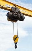 stock photo of crane hook  - Beam crane with engine and hook hanging on steel ropes over cloudy sky background - JPG