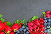 stock photo of berries  - border  of fresh ripe  berries with green  leaves with copy space  on black stone background - JPG