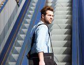 image of escalator  - Portrait of a cool guy standing on escalator - JPG