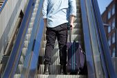 pic of escalator  - Rear portrait of a young man standing on escalator with bag - JPG