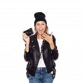 stock photo of beanie hat  - Happy hipster girl in black beanie having fun with vintage noname camera - JPG