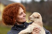 pic of baby goat  - Closeup portrait of a young woman holding a cute baby goat outdoor - JPG
