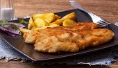 stock photo of cod  - Fried fillet of cod with french fries on a dark plate - JPG