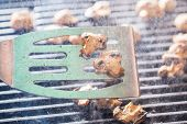 image of champignons  - Champignon white mushrooms on spatula grilled on BBQ with steam and drops of water - JPG