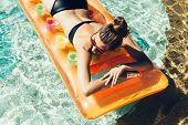 stock photo of woman bikini  - Young pretty fashion woman body posing in summer in pool with clear water lying on mattress in black bikini and having fun - JPG