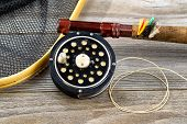 picture of fly rod  - Close up of an antique fly fishing reel rod landing net and artificial flies on rustic wood - JPG
