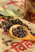 picture of bay leaf  - Wooden spoonful of black pepper seeds and bay leaves on ethnic cloth  - JPG