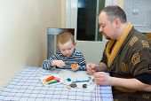 picture of molding clay  - the father and the son sit at a table and are engaged in a molding from color plasticine - JPG