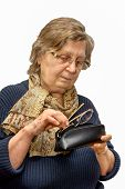 stock photo of early 60s  - old woman in a glasses putting the second glasses into a spectacle case - JPG