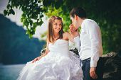 foto of hand kiss  - young fair haired bride sits on rock and groom kisses her hand against azure sea and island - JPG