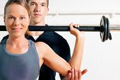 stock photo of personal trainer  - Woman with her personal fitness trainer in the gym exercising power gymnastics with a barbell - JPG