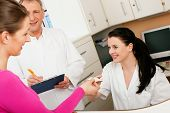 stock photo of over counter  - Patient in reception area of office of doctor or dentist - JPG