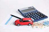 Toy car, money, documents and calculator on table. Car insurance concept poster