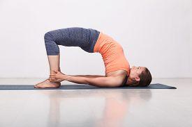 stock photo of ashtanga vinyasa yoga  - Beautiful sporty fit yogini woman practices yoga asana setu bandhasana  - JPG