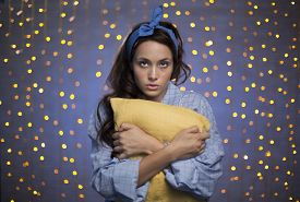 pic of pyjama  - Young female in pyjamas holding pillow and looking at camera on sparkling background - JPG