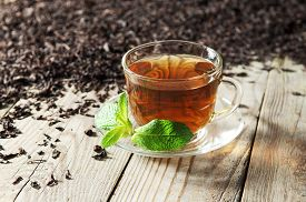 pic of black tea  - Black tea in a glass cup and saucer on a wooden table - JPG