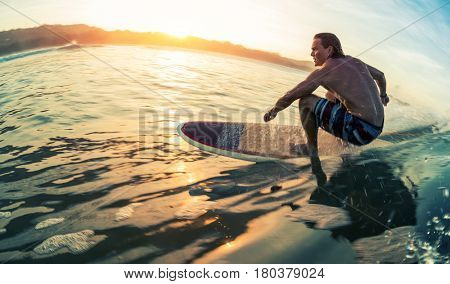 poster of Young man surfs the ocean wave at calm sunrise