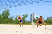Two Men Playing Beach Volleyball - Teenager Falls On Sand To Catch Ball