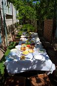 Big Lunch Table With Many Countryside Dishes In Shadow Of Grape Leaves In Hot Sunny Day poster