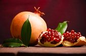 The Pomegranate Is Ripe. Cut Into Pieces Of Ripe Pomegranate. On Wooden Boards. poster
