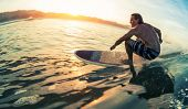 Young man surfs the ocean wave at calm sunrise poster