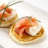 Blini topped with smoked salmon and sour cream.
