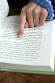 Reading : Index finger pointing on a paragraph of a book