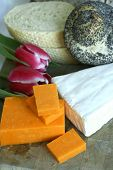 Close up of assorted bread and cheese with tulips on wooden chopping board